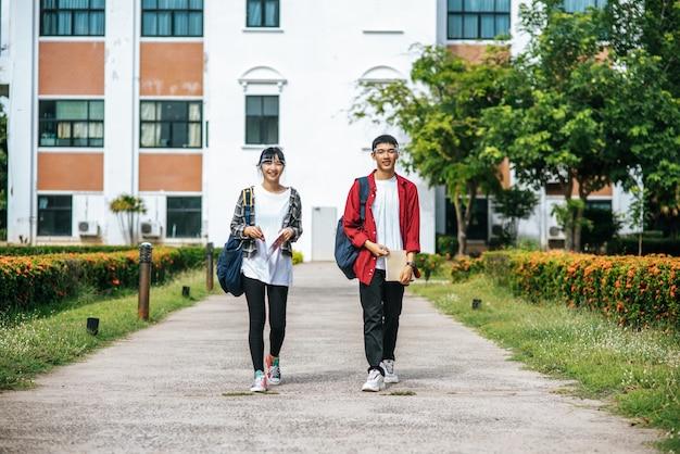 Studenci i studenci noszą twarz chill i stoją przed uniwersytetem.