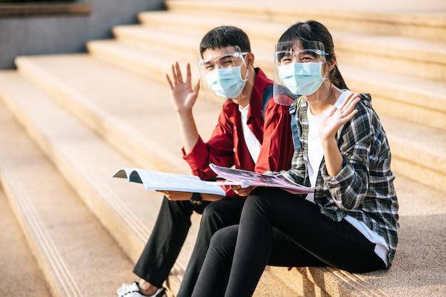 Studenci i uczennice w maskach siedzą i czytają książki na schodach