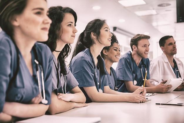 Studenci medycyny słuchają siedząc przy biurku