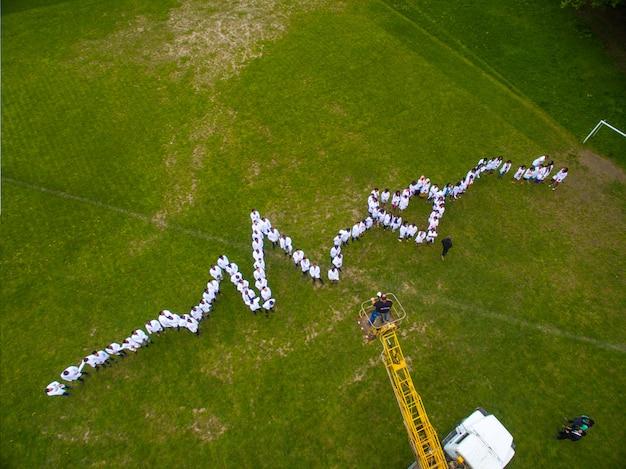 Studenci medycyny stoi na trawie, robi żywemu wykresowi serca.