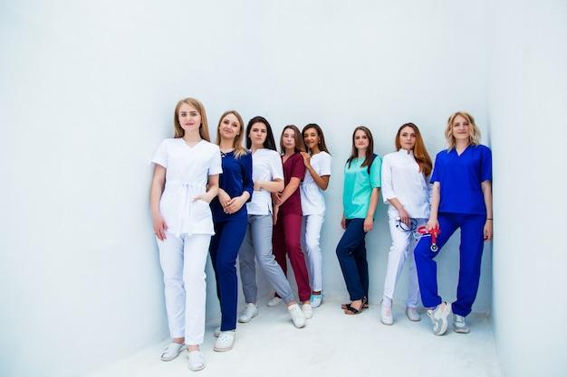 Studenci medycyny, uniwersytet biała ściana tło. grupa profesjonalnych pielęgniarek. zaawansowana szkoła szkoleniowa
