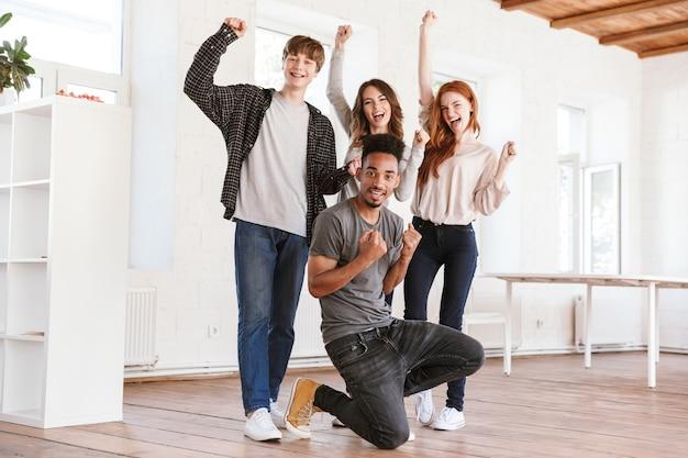 Studenci młodych szczęśliwych przyjaciół wykonują gest zwycięzcy.