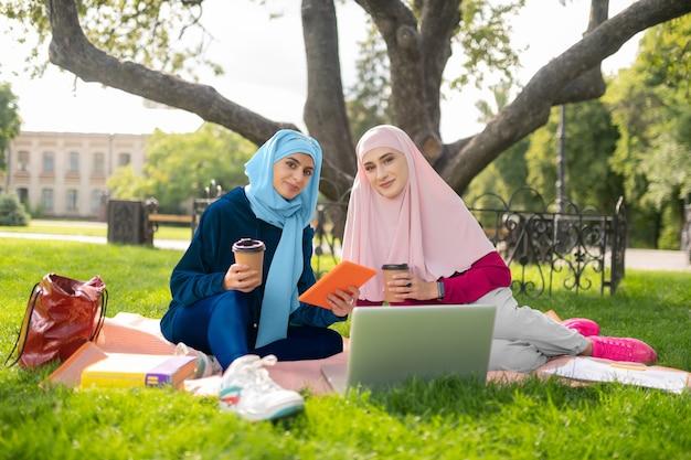 Studenci muzułmańscy. piękni muzułmańscy studenci w hidżabach cieszą się przerwą na zewnątrz w pobliżu uniwersytetu