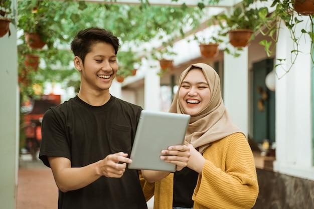 Studenci płci męskiej i hidżabu dziewczyny szczęśliwy, patrząc na ekran tabletu
