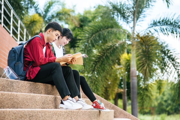 Studenci płci męskiej i żeńskiej siedząc i czytając książki na schodach.