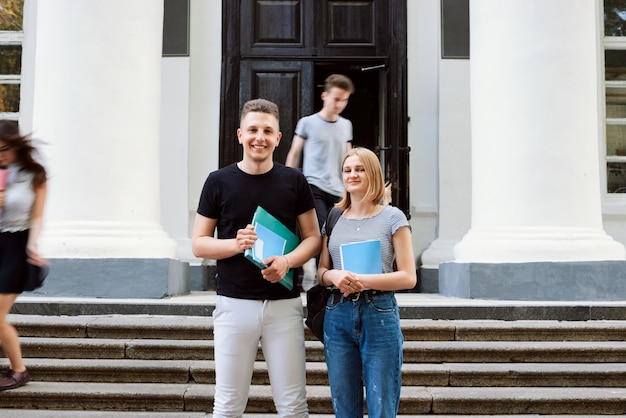 Studenci płci męskiej i żeńskiej z książkami i dokumentami przed zajęciami w pobliżu wejścia do budynku uniwersytetu z kilkoma innymi rozmytymi studentami w ruchu