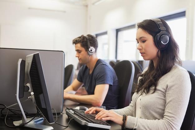 Studenci pracujący w klasie komputerowej
