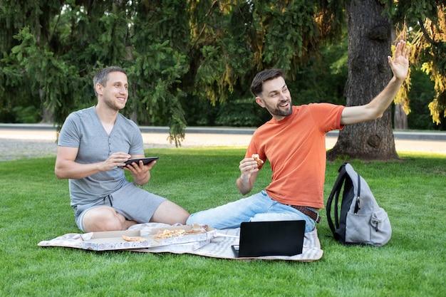 Studenci siedzący zw parku miejskim za pomocą laptopa pracującego na zewnątrz, pokazując gest powitania. szczęśliwy młody człowiek uśmiecha się i macha do przyjaciół. studenci uczący się w parku i uśmiechnięci. przyjaźń, nauka,