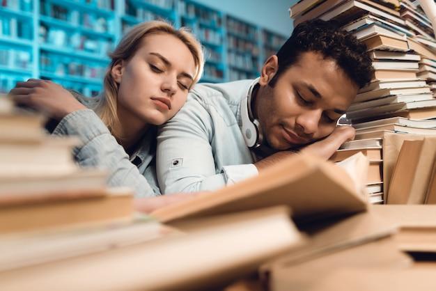 Studenci śpią w bibliotece w nocy.