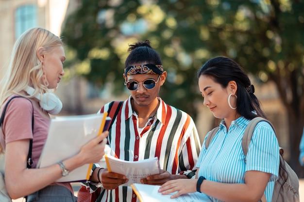 Studenci stojący razem na dziedzińcu uniwersytetu pomagają sobie nawzajem