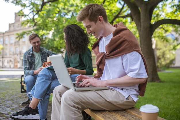 Studenci studiujący w parku i wyglądający na zaangażowanych