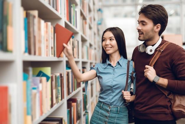Studenci szukają książek w bibliotece.