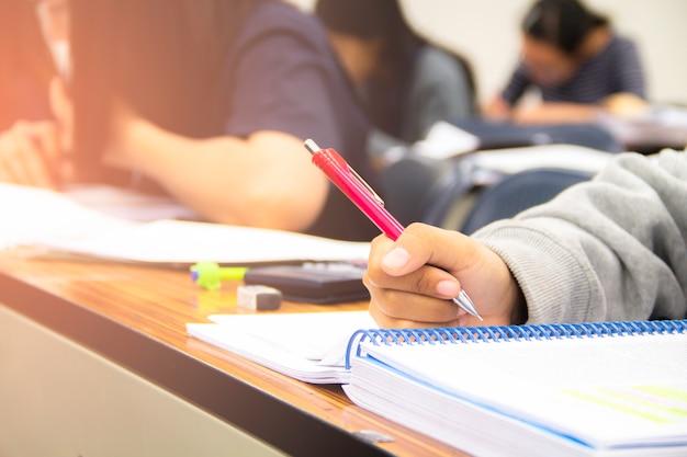 Studenci uniwersytetu robią quizy, testy lub studia od nauczyciela w dużej sali wykładowej. uczniowie w mundurach uczęszczających do szkoły edukacyjnej w klasie egzaminacyjnej.
