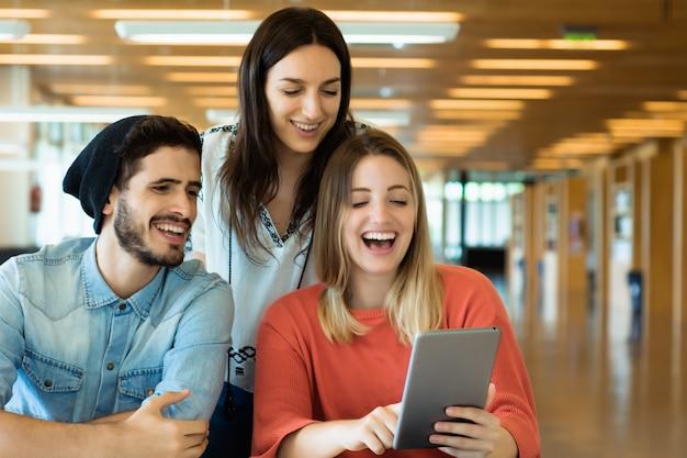 Studenci uniwersytetu używa cyfrowego pastylka w bibliotece uniwersyteckiej.