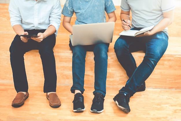 Studenci uniwersytetu używają laptopa spotkanie do pracy domowej badań w kolegium