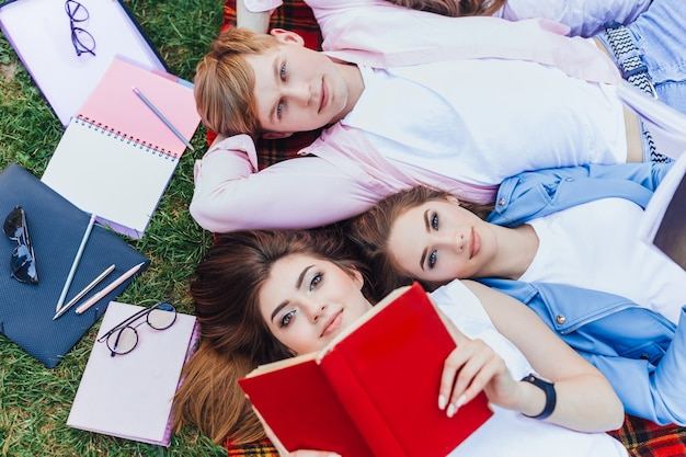 Studenci w kampusie po lekcjach. dwie piękne młode dziewczyny i przystojny chłopak, leżąc na trawie i czytając książkę.