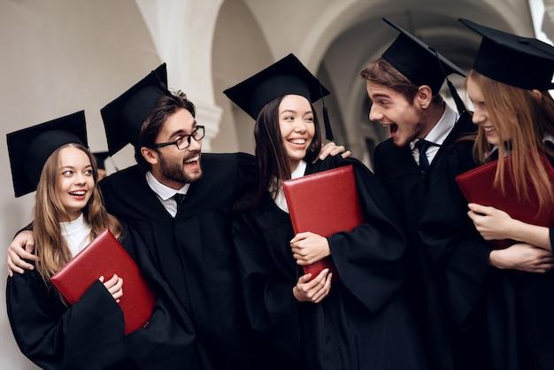 Studenci w płaszczach stoją w korytarzu uniwersyteckim.