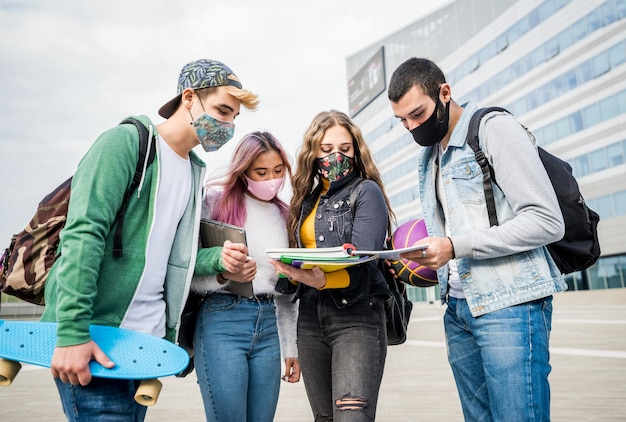 Studenci wielorasowi z maską na twarzy studiujący na kampusie uniwersyteckim