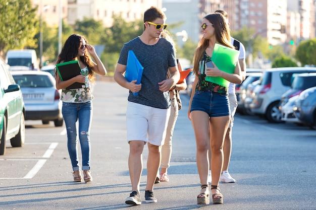 Studenci z teczki chodzenia po ulicy