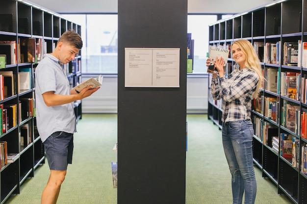 Studenci zbierają książki na półce