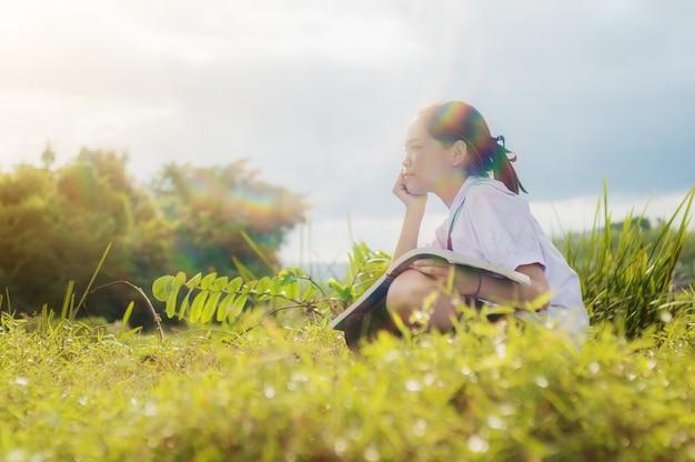 Studencka dziewczyna czyta książkę w złocistej łąkowej contryside naturze