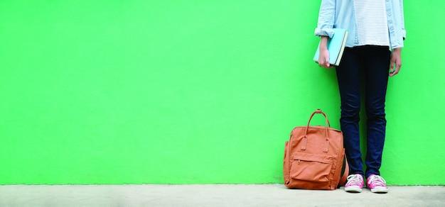 Studencka dziewczyna trzyma książki i szkolną torbę