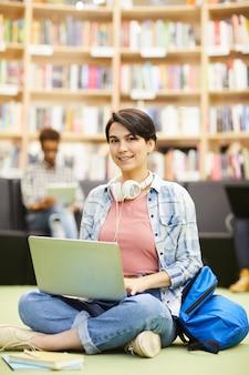 Studencka dziewczyna używa online zasoby na laptopie