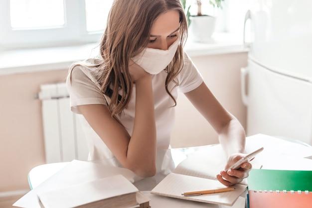 Studencka dziewczyna w medycznej masce siedzi przy stole i trzyma w rękach telefon komórkowy i czyta wiadomości, wiadomości. młoda kobieta freelancer pracuje zdalnie w domu, izoluje kwarantannę,