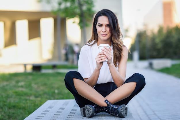 Studencka kobieta bierze kawową przerwę przy uniwersytetem