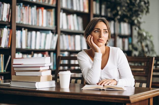 Studencka kobieta studiuje w bibliotece