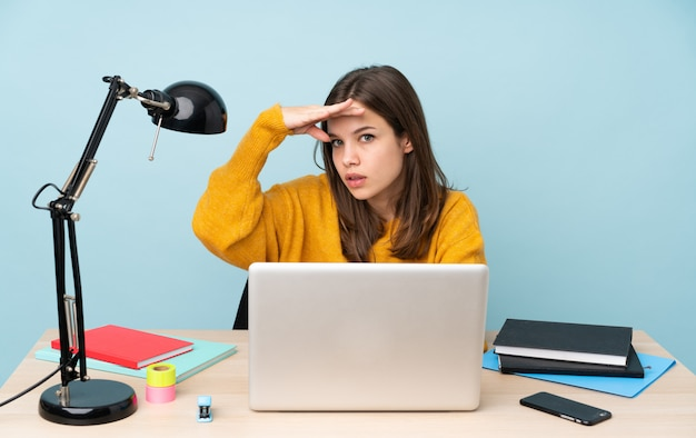 Studencka kobieta studiuje w jej domu odizolowywającym na błękit ścianie patrzeje daleko od ręką patrzeć coś