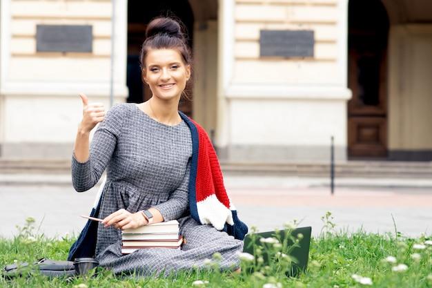 Studencka kobieta z książkami pokazuje aprobaty na trawie