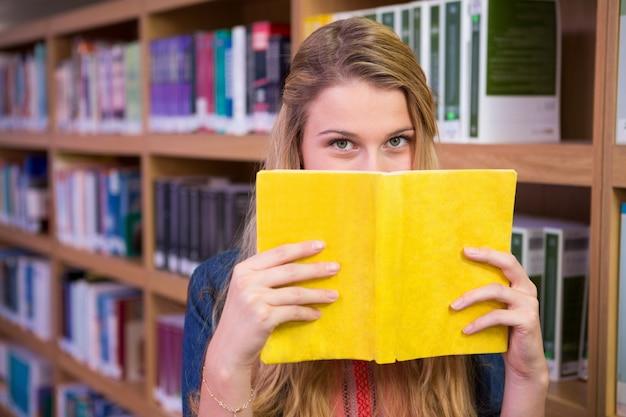 Studencka nakrycie twarz z książką w bibliotece