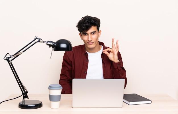 Studencki mężczyzna w miejscu pracy z laptopem
