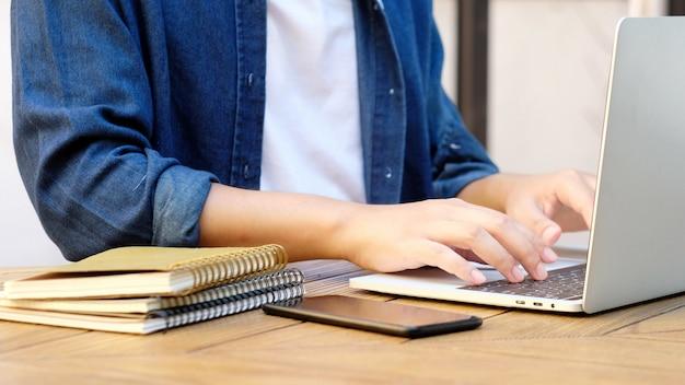 Studencki writing na notatniku podczas gdy używać laptop