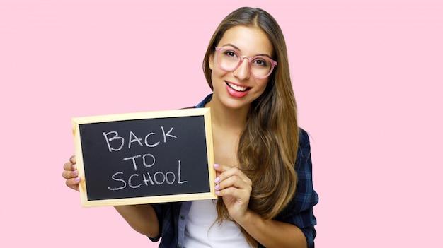 Student college'u pokazując tablicę mówiącą do szkoły