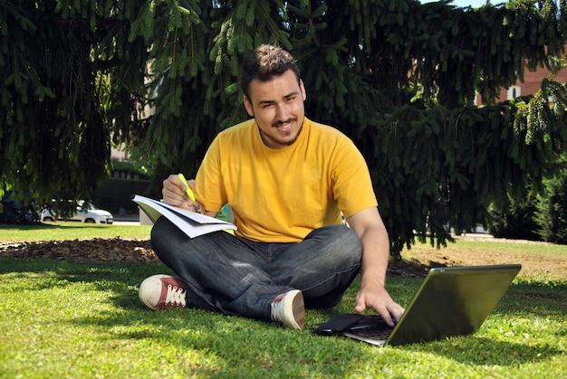 Student collegu kłama na trawie w słońcu z jej komputerem