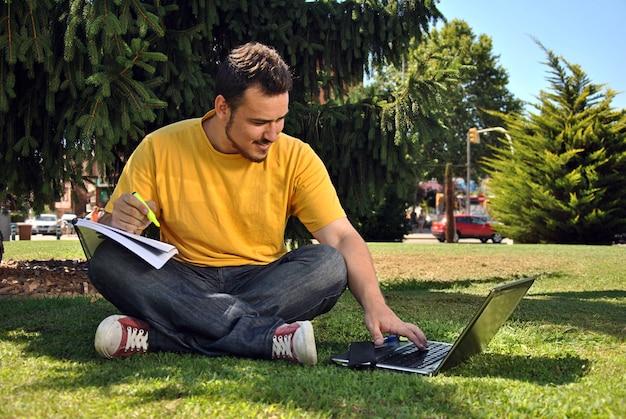 Student collegu kłama na trawie w słońcu z komputerem