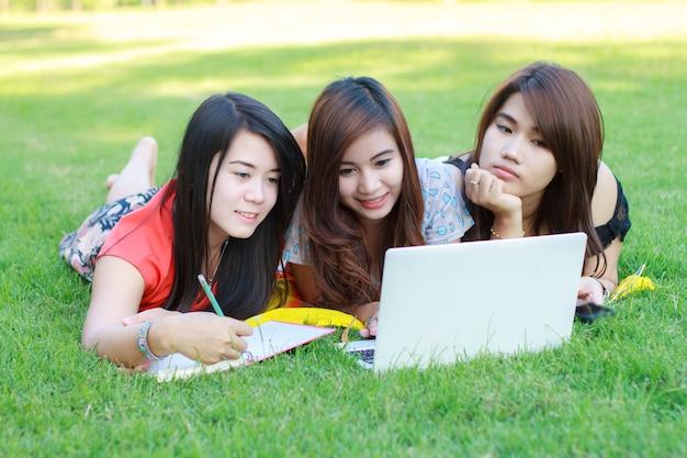 Student collegu łgarski puszek na trawie pracuje na laptopie przy kampusem