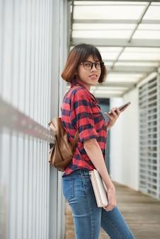 Student collegu pozycja z tylną paczką przy kampusu okno