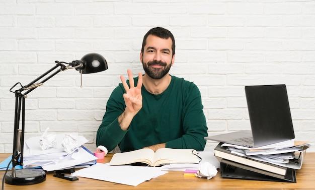 Student człowiek szczęśliwy i licząc trzy palcami