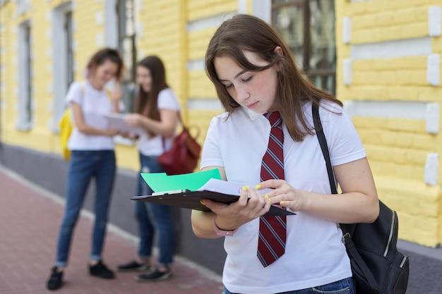 Student dziewczyna nastolatek pozowanie odkryty w białej koszulce z krawatem. tło ceglany budynek, grupa studentów dziewcząt. początek zajęć, powrót na studia, kopia przestrzeń
