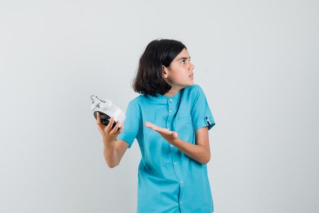 Student dziewczyna pokazuje zegar, prosząc o coś w niebieskiej koszuli i patrząc agresywnie