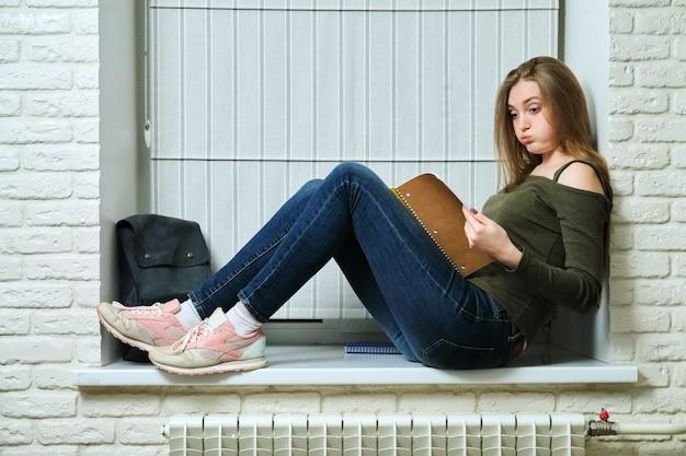 Student dziewczyna siedzi na parapecie, studia, czytanie notebooka. młoda piękna kobieta z plecakiem studentka, edukacja, samokształcenie