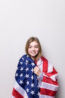 Student dziewczyna trzyma amerykańską flagę na białym tle