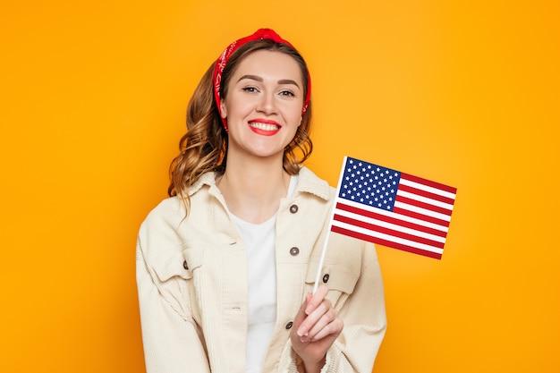 Student dziewczyna trzyma małą amerykańską flagę i uśmiecha się na białym tle na pomarańczowym tle