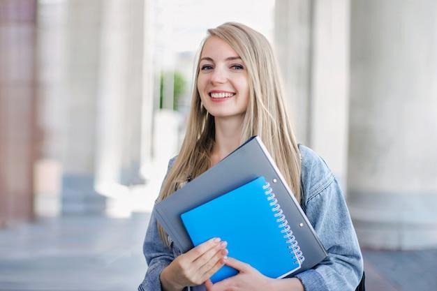 Student dziewczyna trzyma notatnik i uśmiecha się