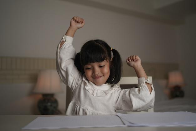 Student dziewczynka ręka podniósł się, aby świętować po odrabianiu lekcji.