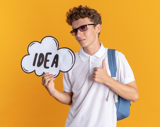 Student facet w codziennej odzieży w okularach z plecakiem, trzymający znak dymek z pomysłem na słowo, patrząc na kamerę pokazującą kciuki do góry, patrząc pewnie, stojąc na pomarańczowym tle
