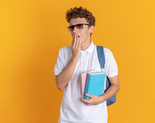 Student facet w swobodnym ubraniu w okularach z plecakiem, trzymający książki, patrzący na bok zdumiony i zaskoczony, zakrywający usta ręką stojącą na pomarańczowym tle